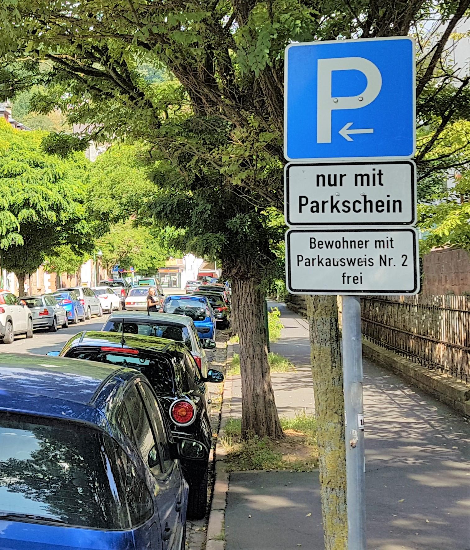 Straße mit parkenden Autos. Nahaufnahme eines Anwohnerparkenschildes.